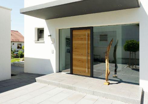 The Art of Haustür – hier realisiert in Form einer DuoLine Vorsatzschalen-Haustür Modell DL 700 mit Oberfläche Alteiche hell 140E und Stock Tiefschwarz, begleitet von zwei großzügigen, rahmenlosen Seitenteilen S99.