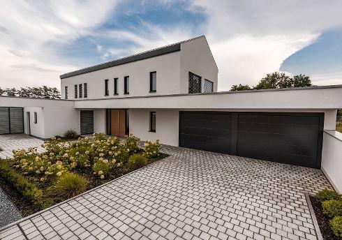 Form follows Kundenwunsch. Und so schmückt dieses Gebäude eine großzügige doppelflügelige Haustür von TRENDTÜREN Modell DS 700 mit echtholzfurnierter Oberfläche in Lärche 152E und Seitenteilen.