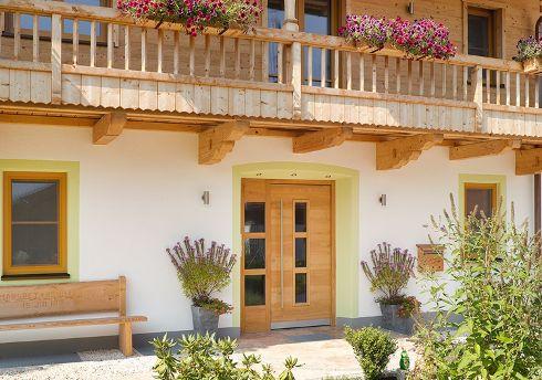 Als individuell maßgefertigte Wunschtüren finden Haustüren von TRENDTÜREN Eingang in jeden Architekturstil – hier als Haustür DS 014 in Sonderausführung mit Holzoberfläche Lärche 151 L und Seitenteil in eine Villa im Landhausstil.